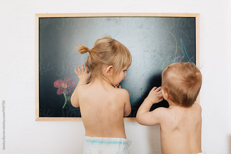 Young siblings drawing with chalk on a chalkboard at home. by Jessica Byrum for Stocksy United