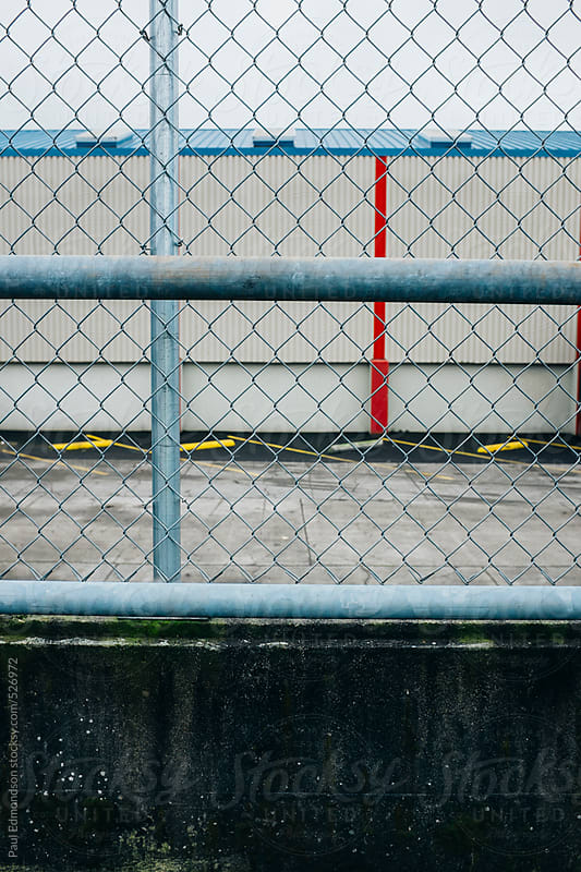 Chain-link fence in front of large industrial warehouse by Paul Edmondson for Stocksy United