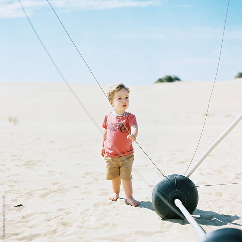 Cute young boy on a sand dune checking out a hand glider by Jakob for Stocksy United
