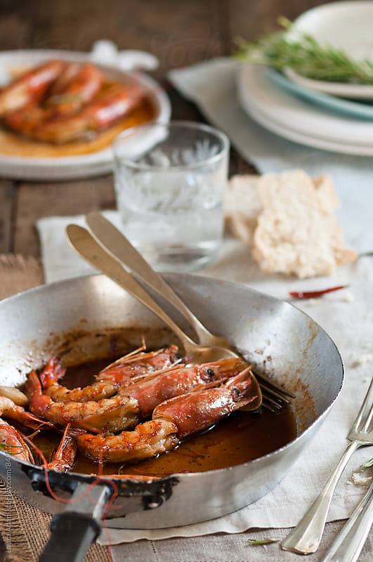 prawns in a pan with honey and rosemary by Laura Adani for Stocksy United