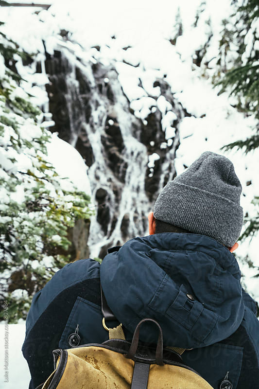 Man In Beanie Standing In Front Of Waterfall In Snowy Forest by Luke Mattson for Stocksy United