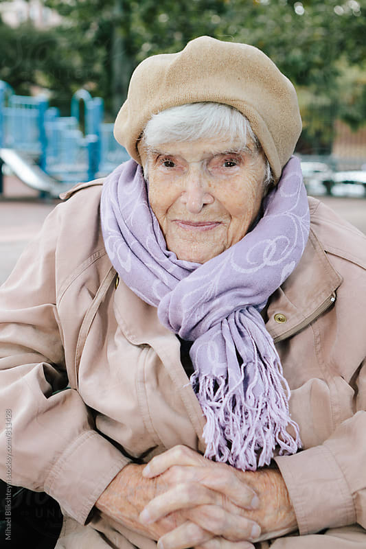 Elderly woman in a fall jacket and matching beige hat and purple scarf sitting in a wheelchair in a park by Mihael Blikshteyn for Stocksy United