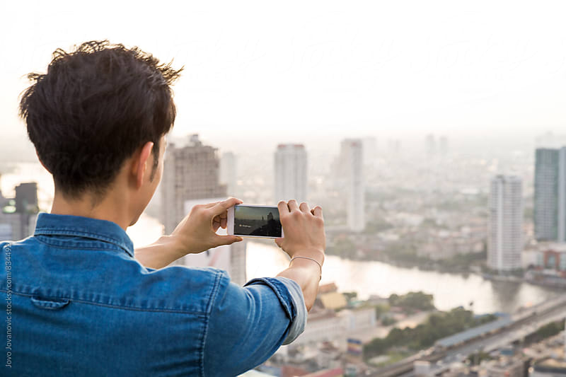 Man taking a photo of city view by Jovo Jovanovic for Stocksy United