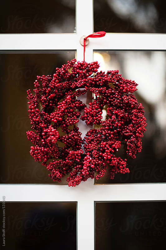 Red berries wreath decorating entrance glass door by Laura Stolfi for Stocksy United