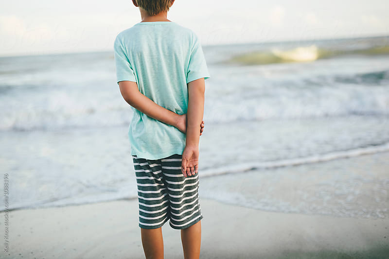 behind a boy looking out at the ocean by Kelly Knox for Stocksy United
