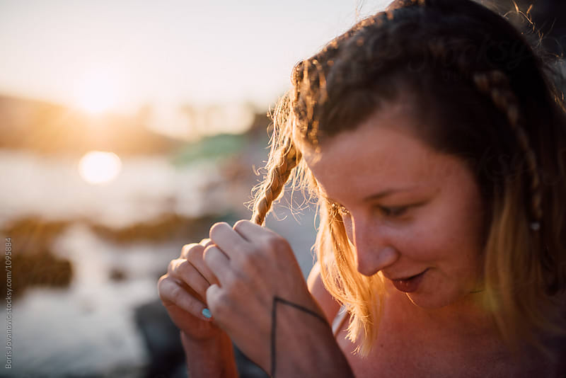 Young woman braiding her hair near the sea by Boris Jovanovic for Stocksy United