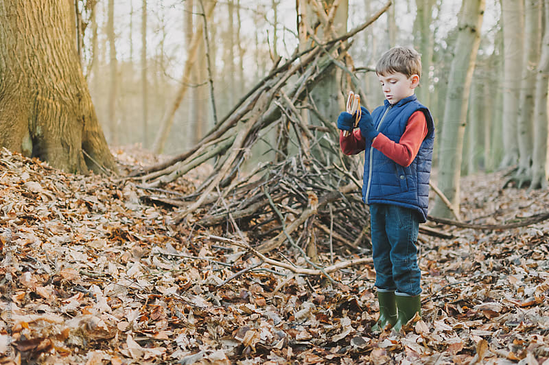 Boy playing in the woods by Rebecca Spencer for Stocksy United