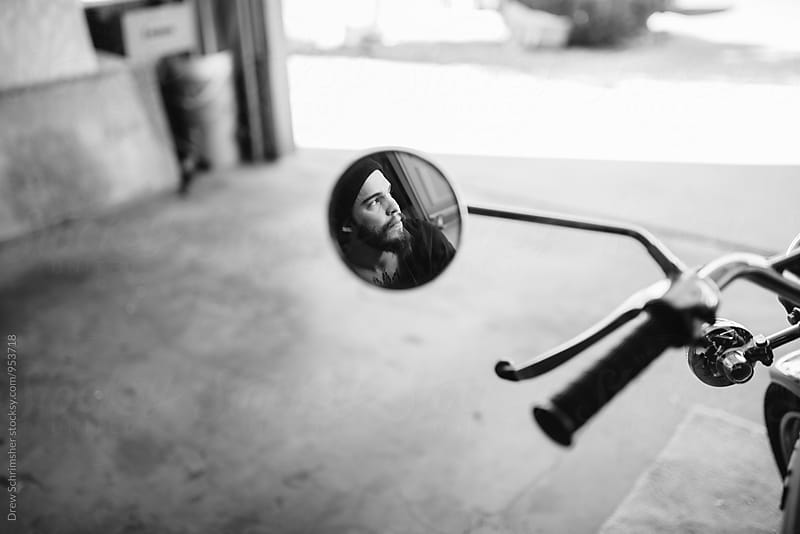 Young man's reflection in motorcycle mirror  by Drew Schrimsher for Stocksy United