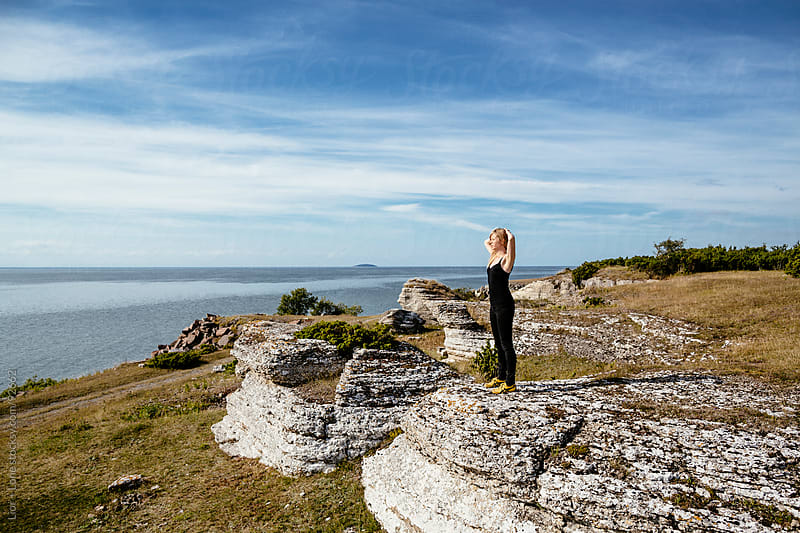 Woman standing on cliff by the sea by Lior + Lone for Stocksy United