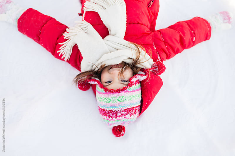 Beautiful young girl wearing bright winter clothes lays in snow, looking at camera by Amanda Worrall for Stocksy United