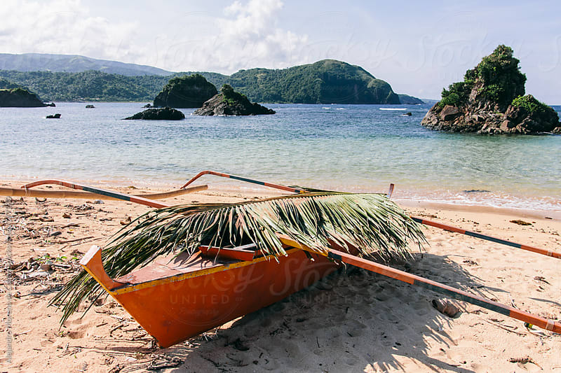 Traditional asian boat covered with palm leaf on a tropical beach by Alejandro Moreno de Carlos for Stocksy United
