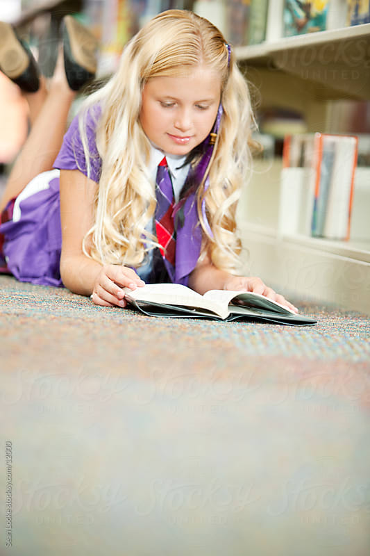 Library: Girl Lies on Floor to Read by Sean Locke for Stocksy United