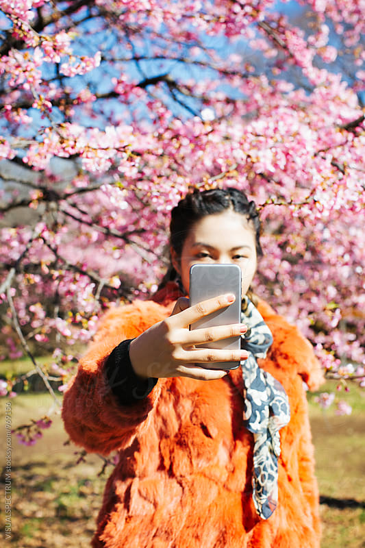Young Japanese Woman Taking Selfie in Front of Blossoming Sakura Tree by Julien L. Balmer for Stocksy United