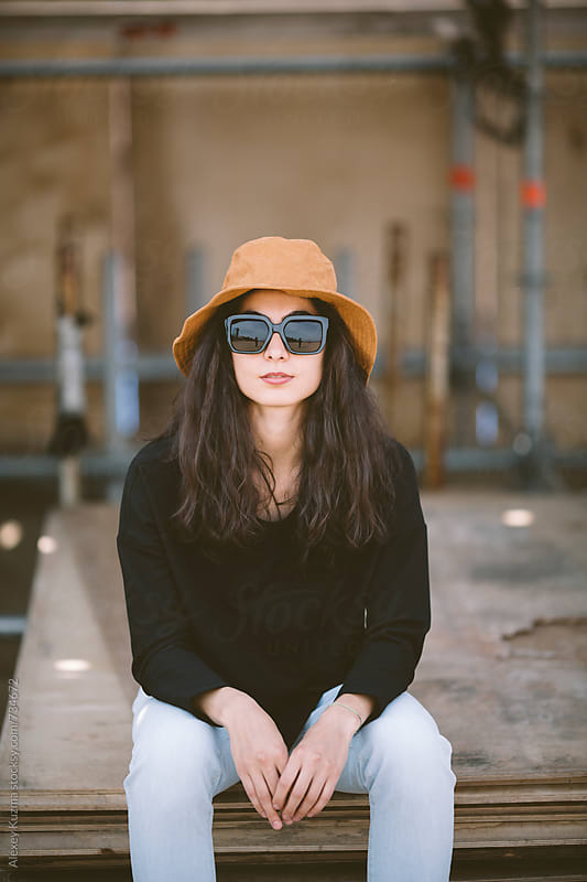 portrait of real young woman with hat and sunglasses by Alexey Kuzma for Stocksy United