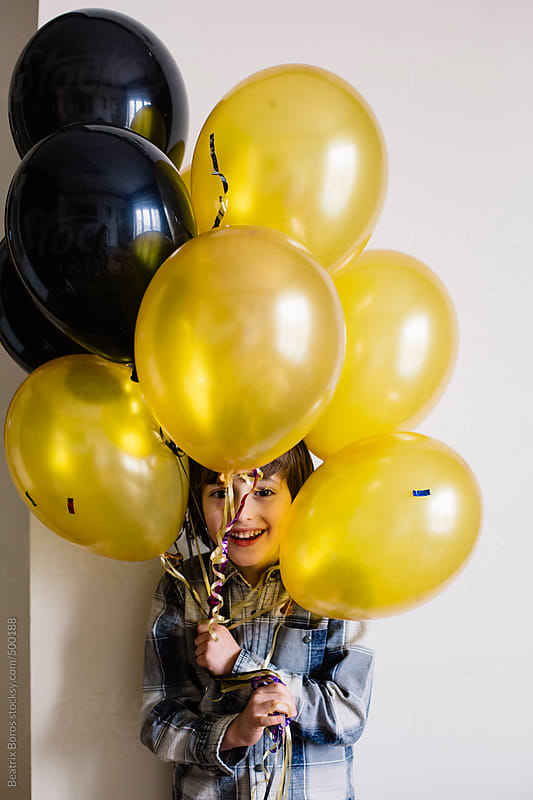 Little boy's head among party balloons by Beatrix Boros for Stocksy United