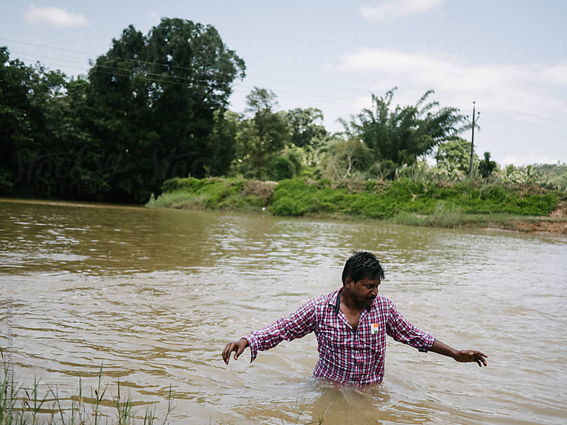 Indian man standing in dirty river by Martin Matej for Stocksy United