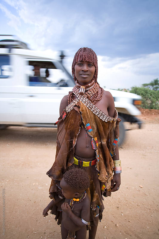 Mother and Child from Hamer tribe, truck passing in background. by Hugh Sitton for Stocksy United
