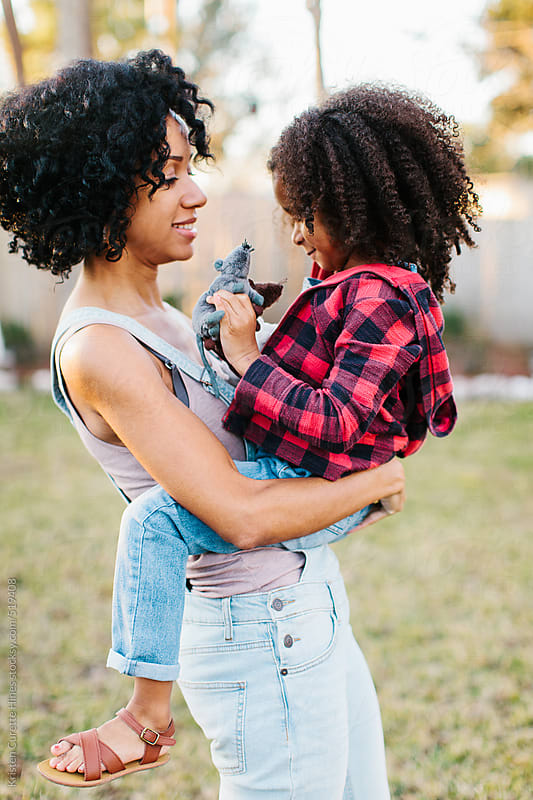 A mother and daughter playing outdoors in their back yard by Kristen Curette Hines for Stocksy United