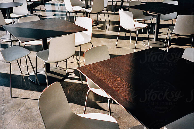 Empty White Chairs and Dark Wood Tables in Soft Warm Light by Austin Rogers for Stocksy United