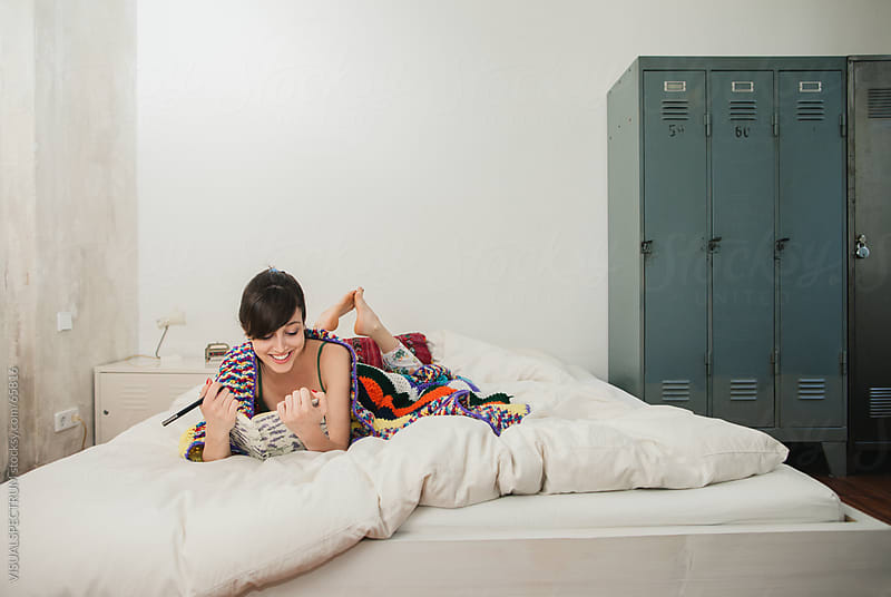 Young Woman Reading on Bed by Julien L. Balmer for Stocksy United