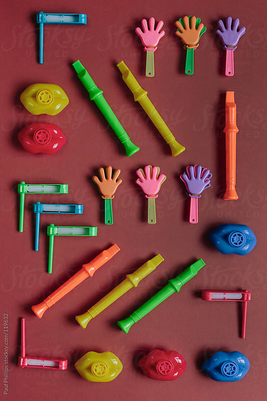 Miniature musical toy instruments on a red background by Paul Phillips for Stocksy United