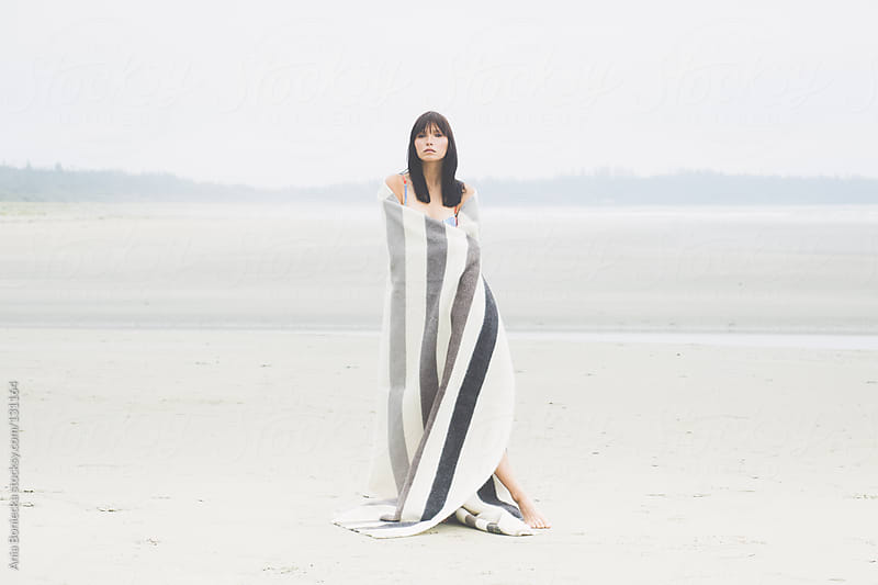 A woman wrapped in a blanket standing on a desolate beach by Ania Boniecka for Stocksy United