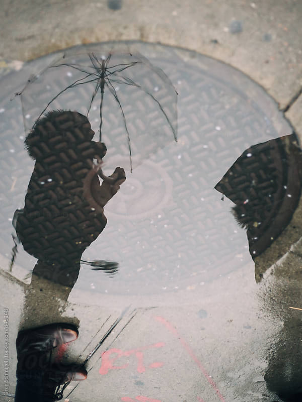A reflection of a person holding an umbrella on a rainy city sidewalk by Greg Schmigel for Stocksy United