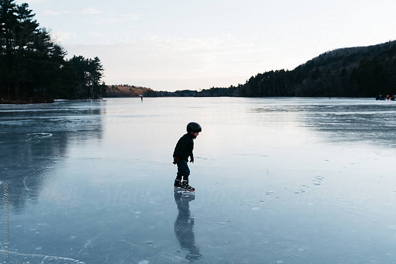 little kid skating on a lake by Léa Jones for Stocksy United