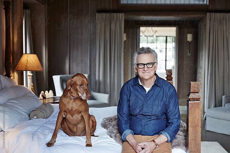 Mature man with grey hair relaxing with his dog in bedroom by Trinette Reed for Stocksy United