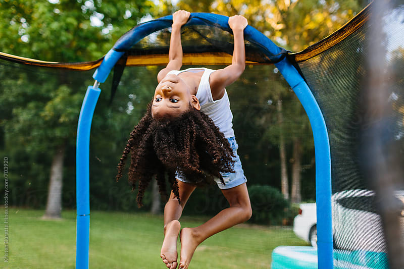 A small toddler girl hanging the side of her trampoline by Kristen Curette Hines for Stocksy United