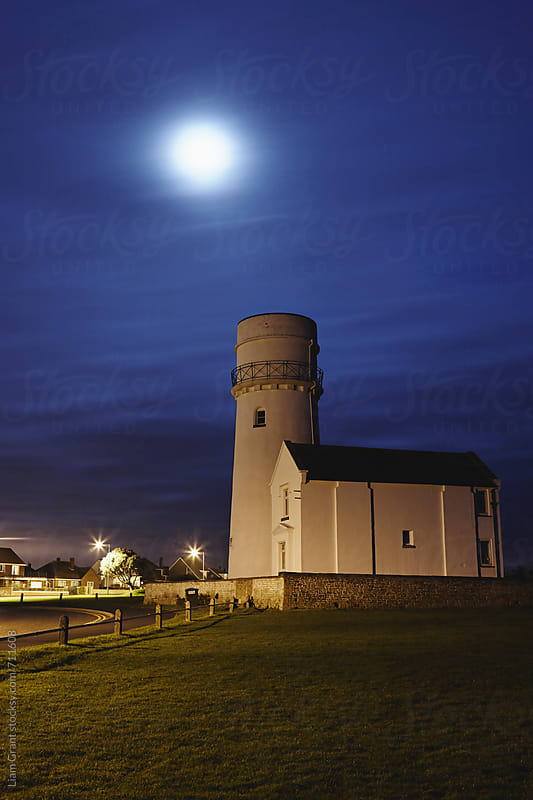 Moon over lighthouse at dawn. Old Hunstanton, Norfolk, UK. by Liam Grant for Stocksy United