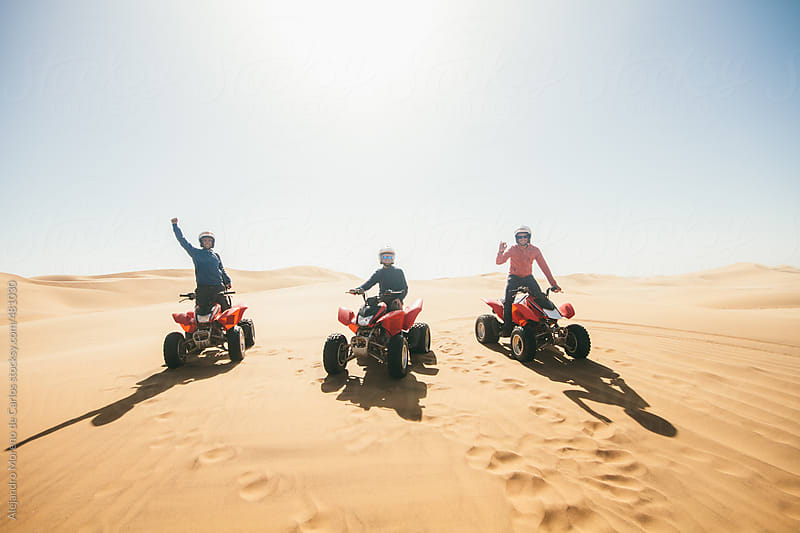 Group of three friends on ATV on sand dunes in desert landscape - Adventure travel by Alejandro Moreno de Carlos for Stocksy United