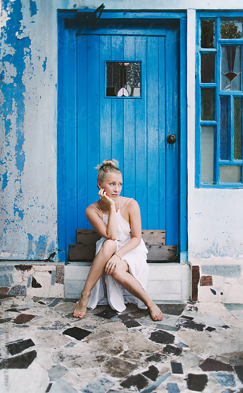 Young beautiful blond woman sitting in front of bright blue door by Nabi Tang for Stocksy United