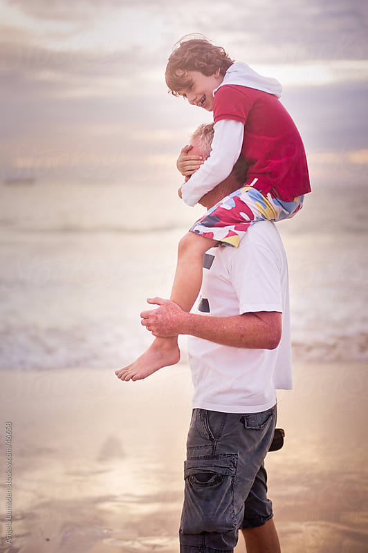 Boy being carried on his father's shoulders at beach at sunset by Angela Lumsden for Stocksy United