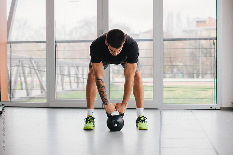 Man lifting a kettle bell indoor by Marija Mandic for Stocksy United