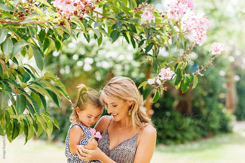 Mother holding daughter playing in park by Image Supply Co for Stocksy United