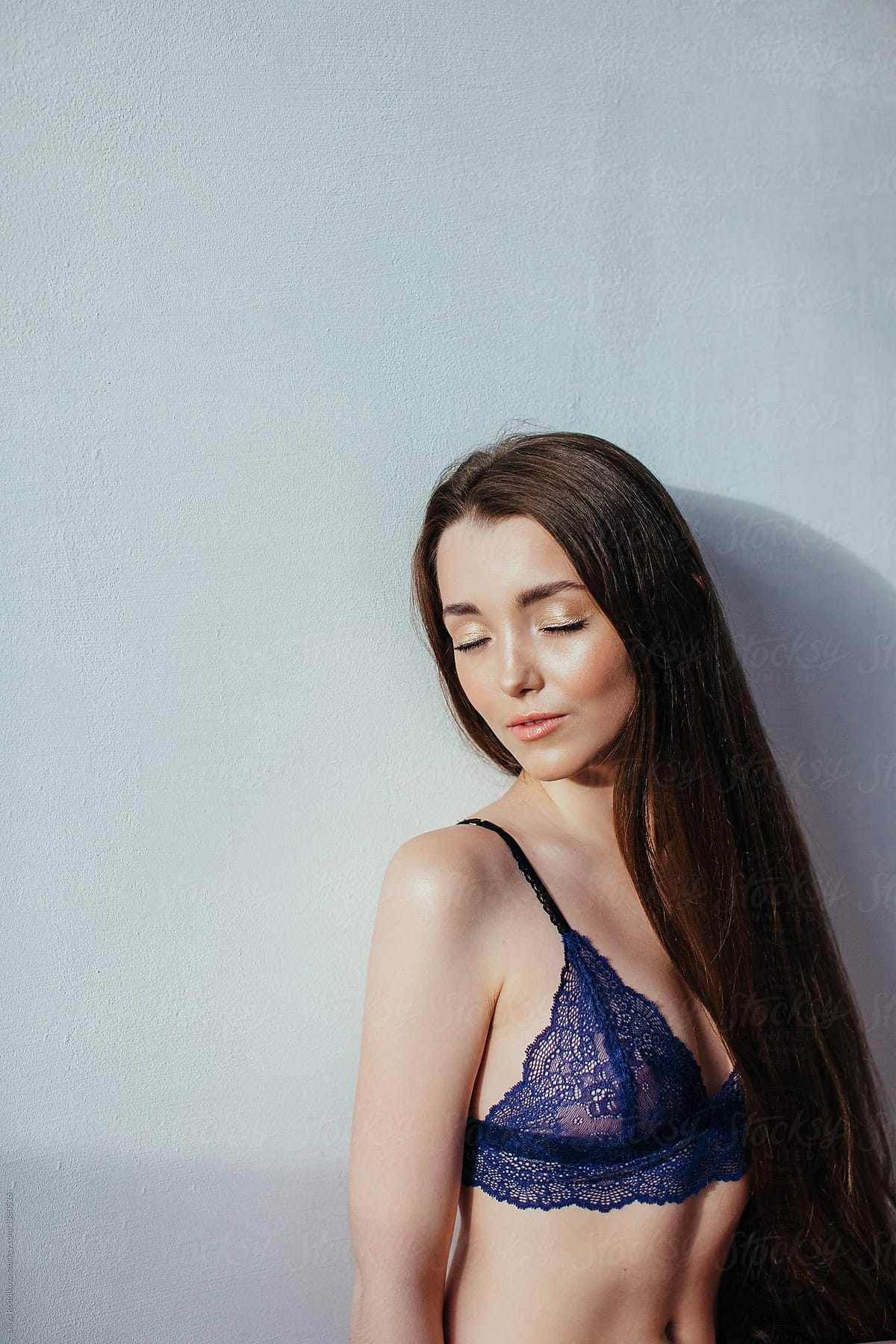 479cfebe051 Portrait of young female with long beautiful hair and closed eyes wearing  lace blue bra