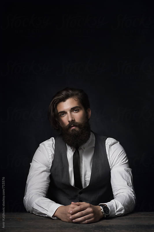 Dark portrait of a stylish man by Amir Kaljikovic for Stocksy United