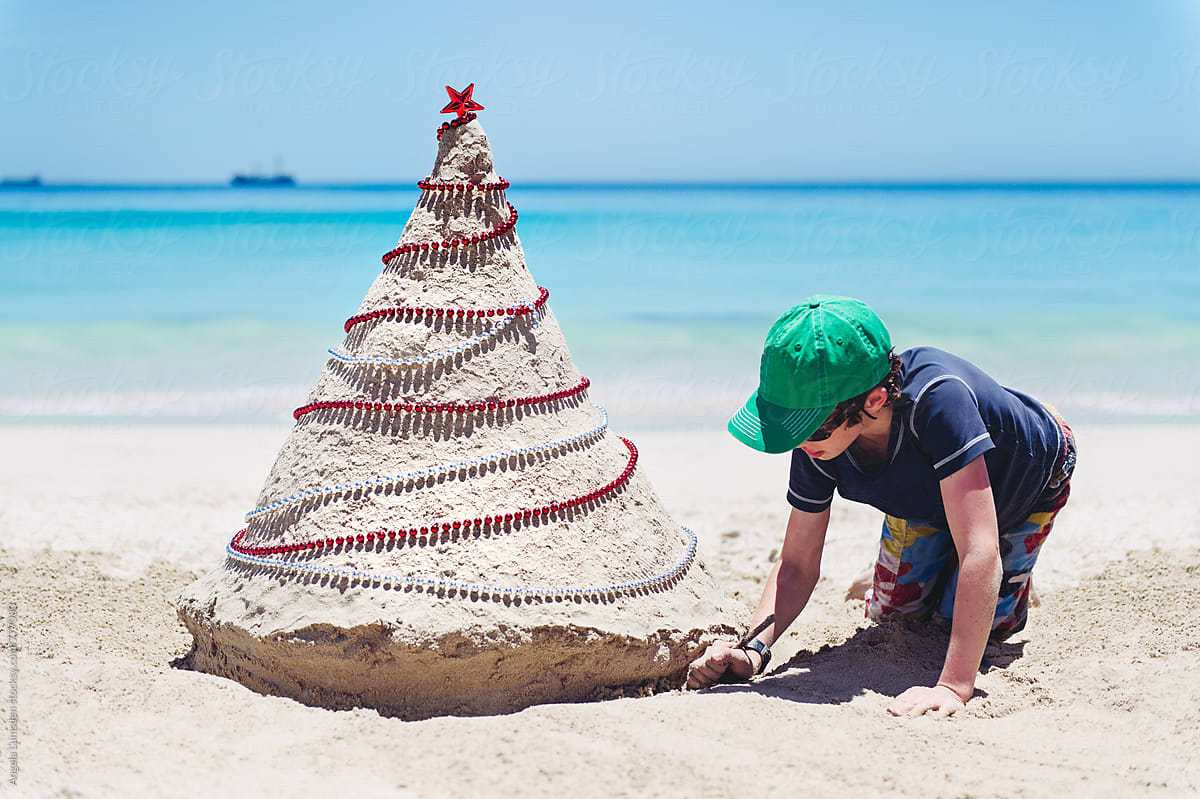 Beach Christmas.Boy Making A Large Sand Christmas Tree At The Beach In