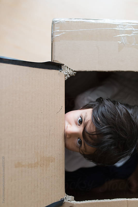 young child inside a box peeking out by Tara Romasanta for Stocksy United