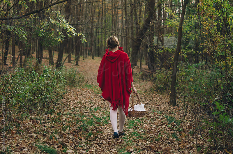 girl in red with basket walking in woods by Deirdre Malfatto for Stocksy United