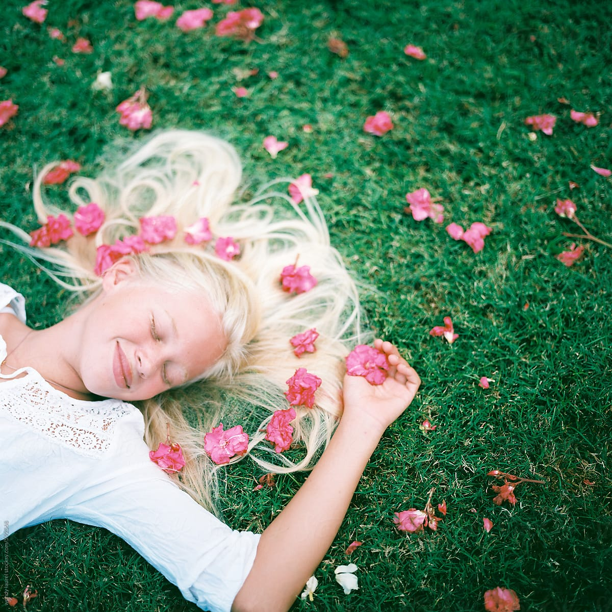 Blonde girl laying in green grass with pink flowers stocksy united blonde girl laying in green grass with pink flowers by wendy laurel for stocksy united mightylinksfo