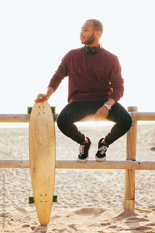Casual man with his longboard on beach in a sunny day. by BONNINSTUDIO for Stocksy United