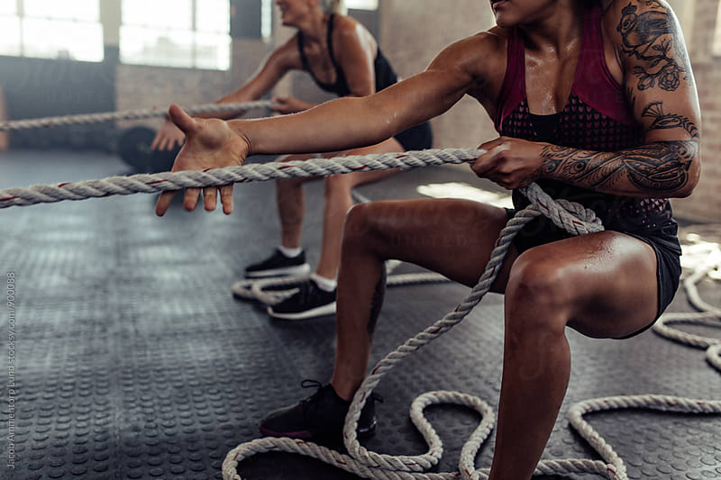 Women doing intense workout at gym by Jacob Lund for Stocksy United