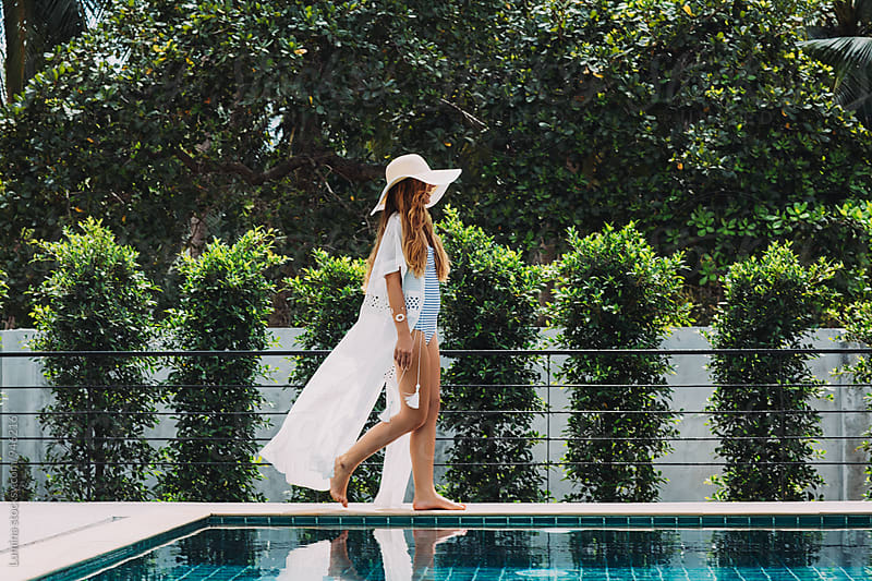 Woman Walking by a Swimming Pool by Lumina for Stocksy United