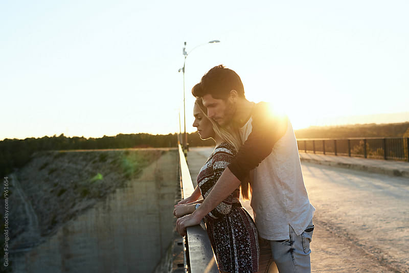 Bearded boyfriend standing behind his girlfriend on bridge by Guille Faingold for Stocksy United
