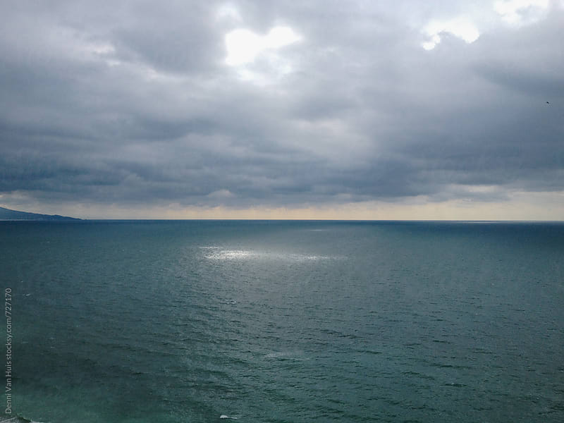 A beam of sunlight shines through the clouds onto the ocean. by Denni Van Huis for Stocksy United