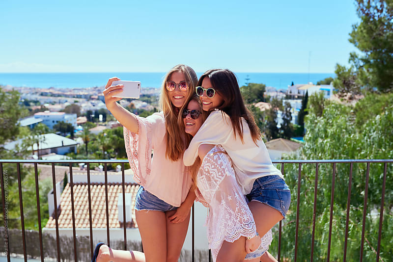 Smiling girlfriends taking selfie against of cityscape by Guille Faingold for Stocksy United