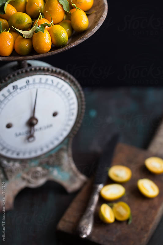 Kumquats on an antique scale by Aniko Lueff Takacs for Stocksy United