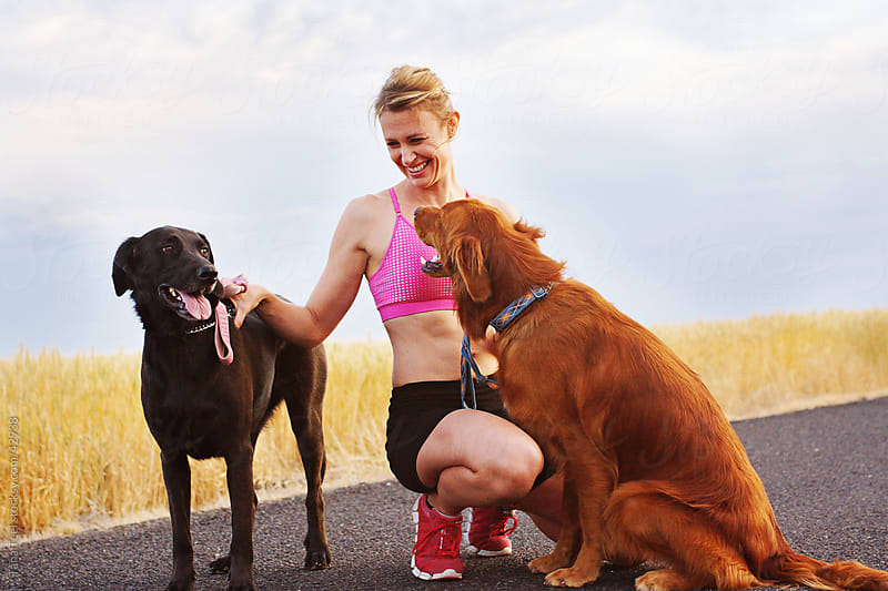 Woman runner with her dogs by Tana Teel for Stocksy United